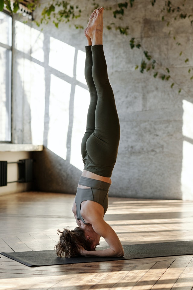 Woman doing a head stand during her online classes for yoga